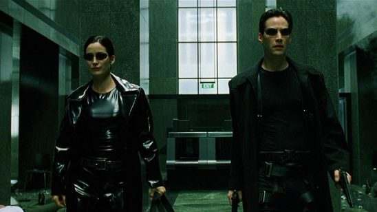 In the Matrix, Trinity and Neo are in a lobby with dramatic black clothes and holding two guns each