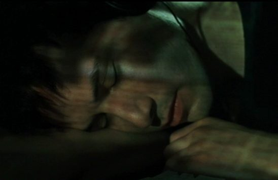 Neo sleeps at his desk with the glow of his computer screen over his face