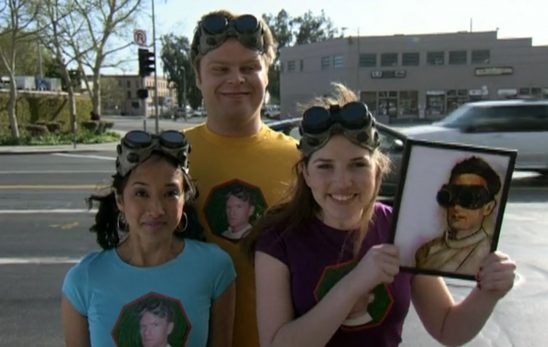 The three fans who were previously treasuring a hair sample from Captain Hammer are not holding up a picture of Dr. Horrible