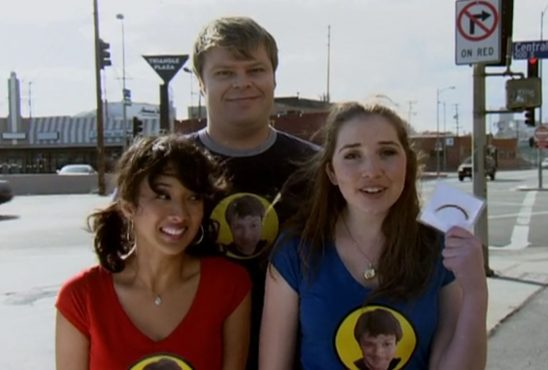 Three fans wear t-shirts with Captain Hammer on them. One proudly holds up a lock of his hair.