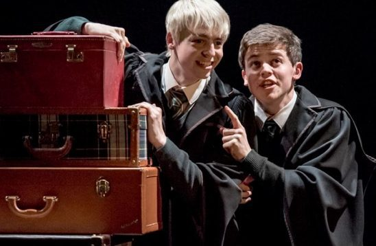 Scorpius and Albus hide behind a stack of suitcases