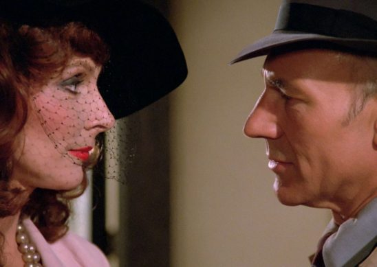 Crusher and Picard, dressed up in 40s outfits, gaze at each other