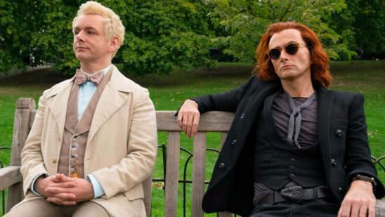 An angel and demon in human form sit next to each other on a bench in Good Omens