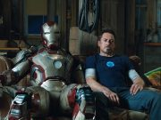 Tony Stark sitting on a couch next to his suit.