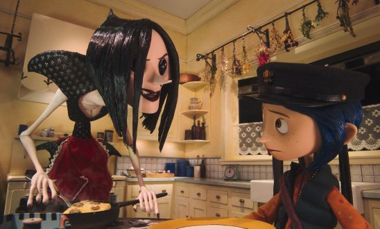 Coraline frowns as she sits at the table with Other Mother, a monster with button eyes