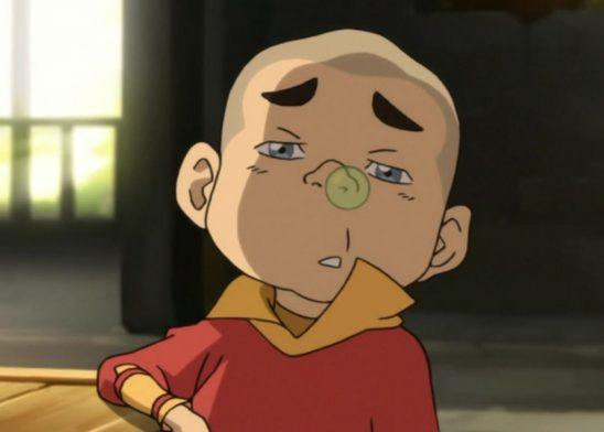 A young boy with a snot bubble on his nose.