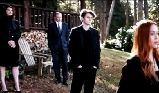 Several characters at Tony Stark's funeral, with a teenaged boy in the foreground.