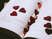 Red paper hearts spread over an open book
