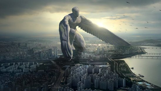 An Angel statue standing over a city.
