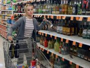 Eleanor from the good place grabbing alcohol off a grocery store shelf