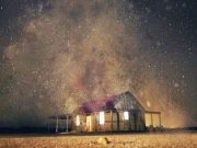 A house with glowing dust coming from the windows, beneath a starry sky on the cover of Agents of Dreamland